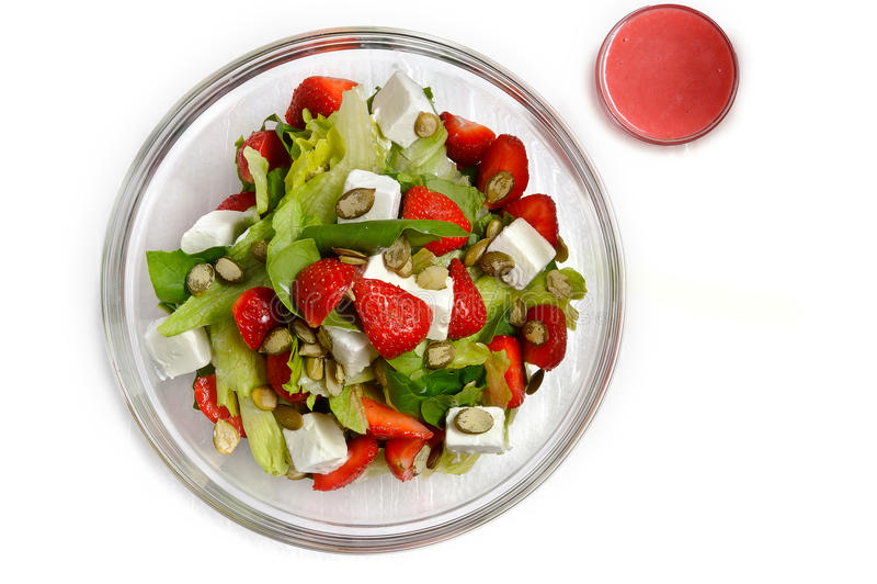 Sallad i pozrachnoy platta med jordgubbar, solrosfrö, ost, gräsplaner och sås arkivbilder