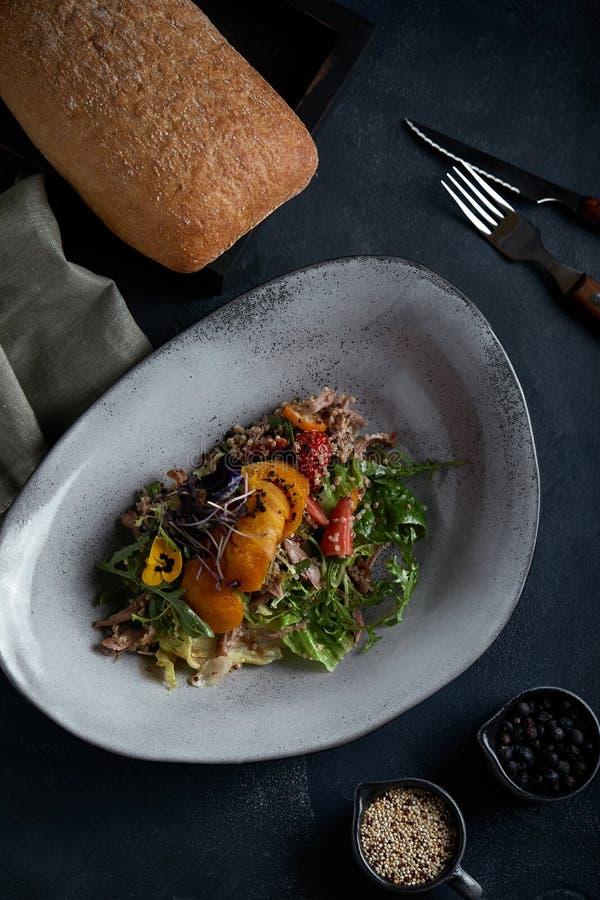 Sallad med andjordgubbar och mango på en mörk bakgrund, låg tangent Matfotobegrepp Restaurangmat, mat royaltyfria bilder