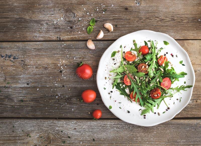 Sallad med arugula, körsbärsröda tomater, solrosfrö och örter på den vita keramiska plattan över lantlig wood bakgrund, bästa sik royaltyfri fotografi