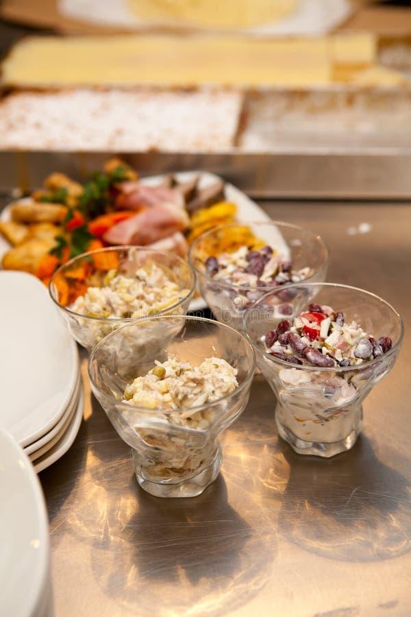 Sallad med bönor, efterrätt och grönsaker och kött i kök fotografering för bildbyråer