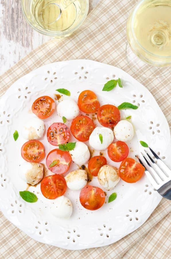 Sallad med den mini- mozzarellaen, körsbärsröda tomater, ny basilika, bästa sikt royaltyfri bild