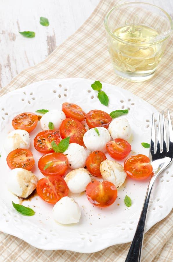 Sallad med den mini- mozzarellaen, körsbärsröda tomater och ny basilika arkivbilder