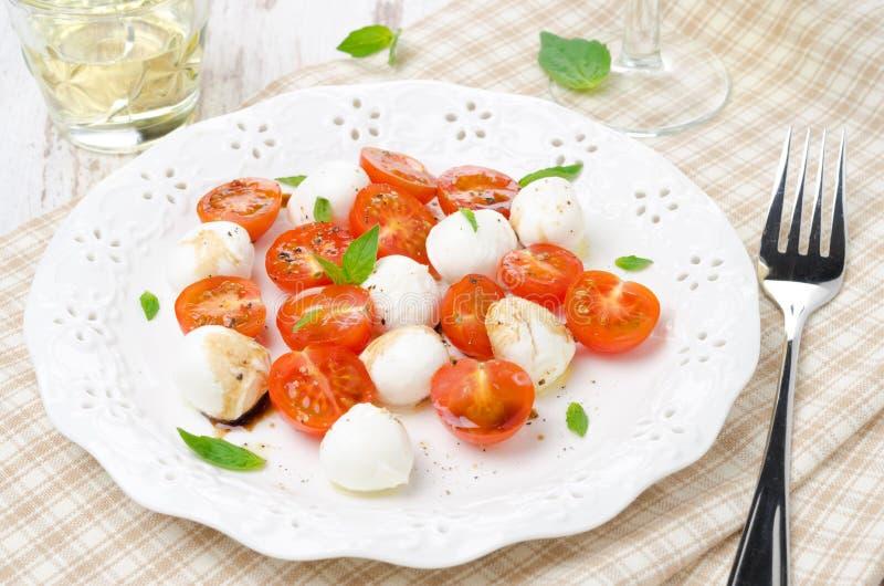 Sallad med den mini- mozzarellaen, tomater och ny basilika royaltyfria bilder