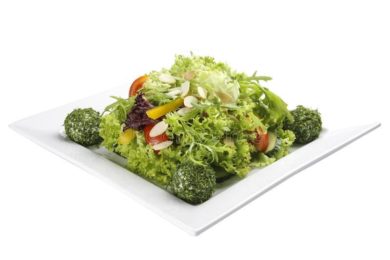 Sallad med grönsaker och ostbollar på en vit platta royaltyfri bild
