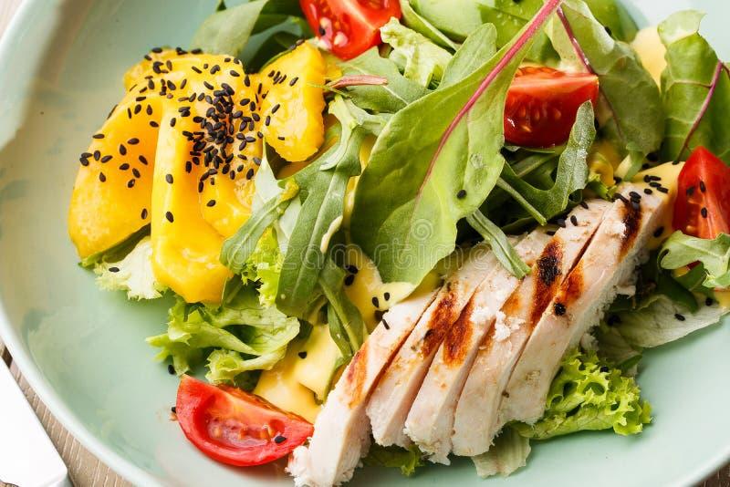 Sallad med grillad höna, mango, grönsallat, avokado, tomater, arugula, ostsause på en vit platta på trä arkivfoto
