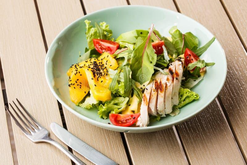 Sallad med grillad höna, mango, grönsallat, avokado, tomater, arugula, ostsause på en vit platta på trä royaltyfri foto