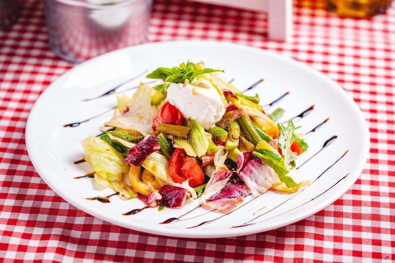 Sallad med haricot vert, tomater, spansk peppar, ricottaost och blandade gräsplaner på den vita plattan royaltyfri foto
