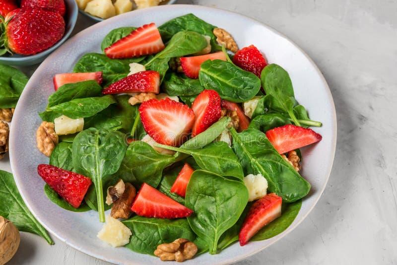 Sallad med jordgubben, spenatsidor, parmesanost och valn?tter p? konkret bakgrund banta sund mat royaltyfria bilder