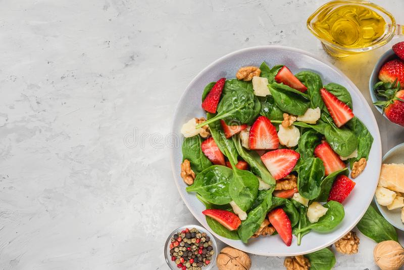 Sallad med jordgubben, spenatsidor, parmesanost, olivolja och valnötter på konkret bakgrund banta sund mat arkivbilder