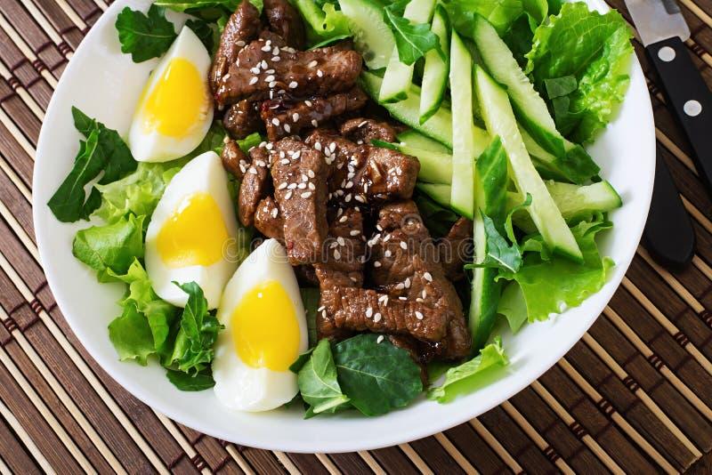 Sallad med kryddigt nötkött, gurkan och ägg arkivbilder