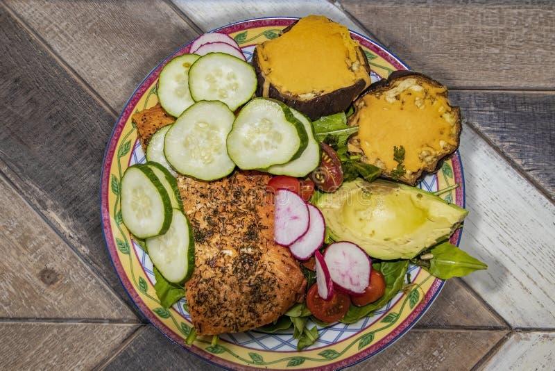 Sallad med laxen och aubergine och gurkor och avacadoen i nätt maträtt på grov diagonal planka ytbehandlar - bästa sikt arkivbild