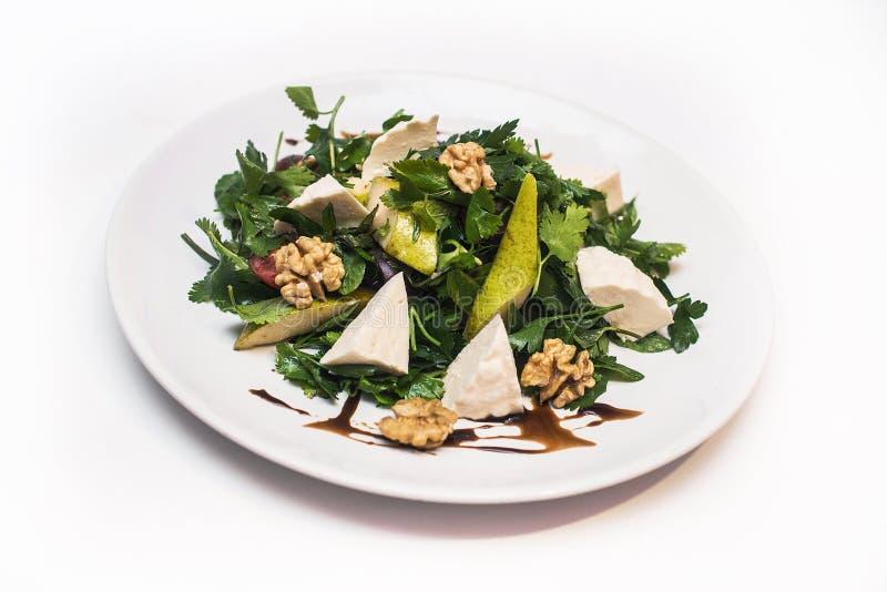 Sallad med päron med ost och valnötter på en vit platta royaltyfri foto