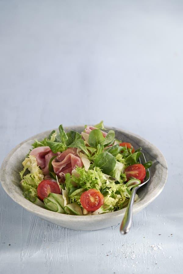Sallad med prosciutto crudo, varierad sallat, körsbär, gurka på ljusbakgrund med plats för text Leveranta livsmedel royaltyfria foton