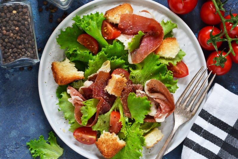 Sallad med prosciuttoen, körsbärsröda tomater, brödchips pÃ¥ köksbordet ovanför sikt royaltyfria bilder