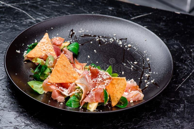 Sallad med prosciuttoen, nachos, tomater, ost och spenat på en svart matte plattanärbild på en mörk bakgrund arkivfoton
