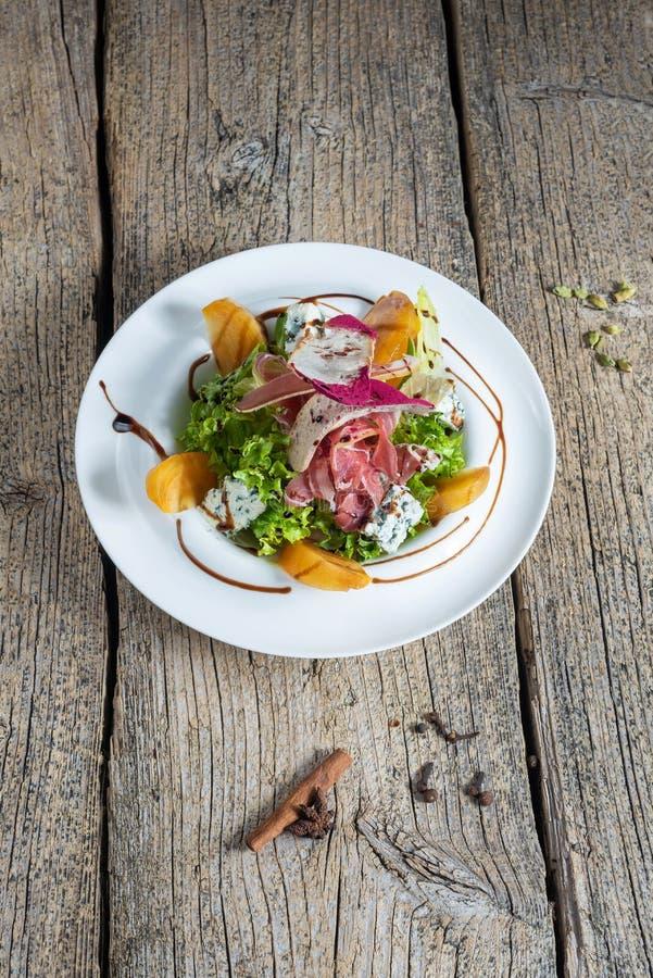 Sallad med skivor av bacon, persimonet och stycken av gorgonzola framläggas beautifully på en vit platta royaltyfria bilder