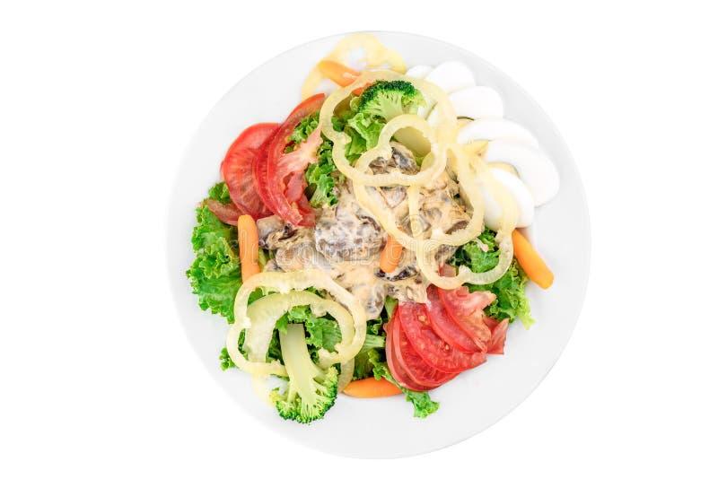 Sallad med tomater, spansk peppar, champinjoner, det kokta ägget, broccoli och morötter i en vit platta royaltyfri bild