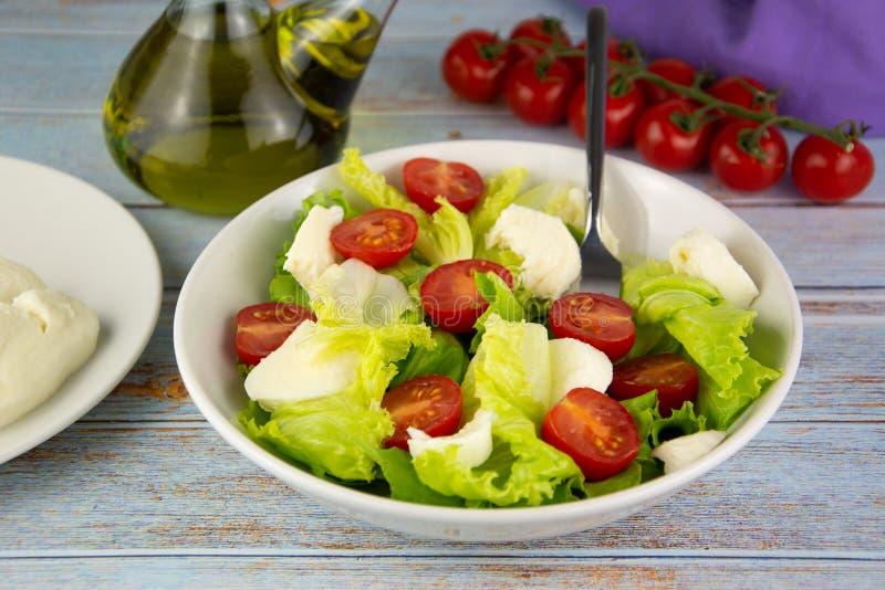 Sallad med tomatost och grönsallat, dietisk mat som kryddas med spansk olivolja fotografering för bildbyråer