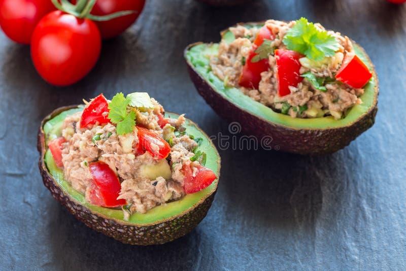 Sallad med tonfisk, avokadot, tomater, koriander och citronjuice som tj?nas som i avokadobunkar, ingredienser p? bakgrund som ?r  royaltyfri fotografi
