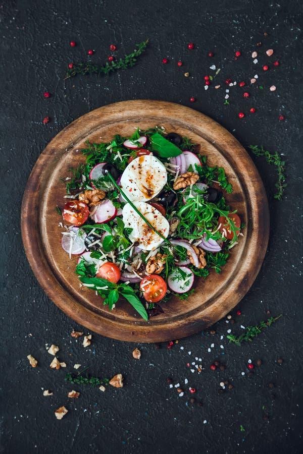 Sallad på en rund trästyckningsdel Ingredienser: mjukt kokt ägg, rädisa, körsbärstomater, gröna, röda lök, arugula, dill, royaltyfria foton