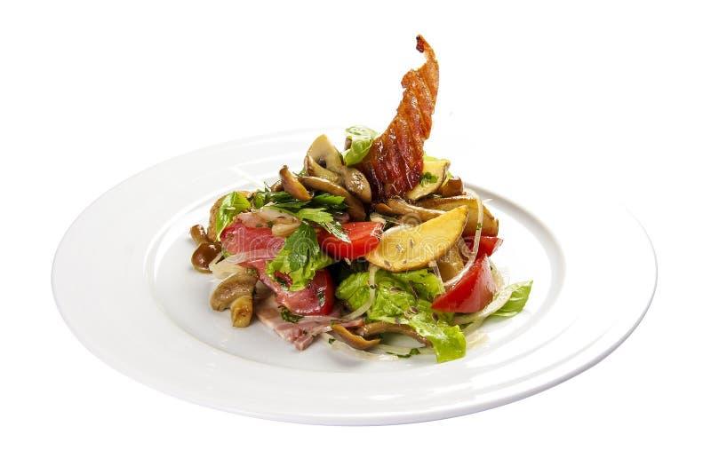 Sallad 'Slavkovsky ', Varm sallad med bacon, potatisar, gräsplaner och champinjoner arkivfoto