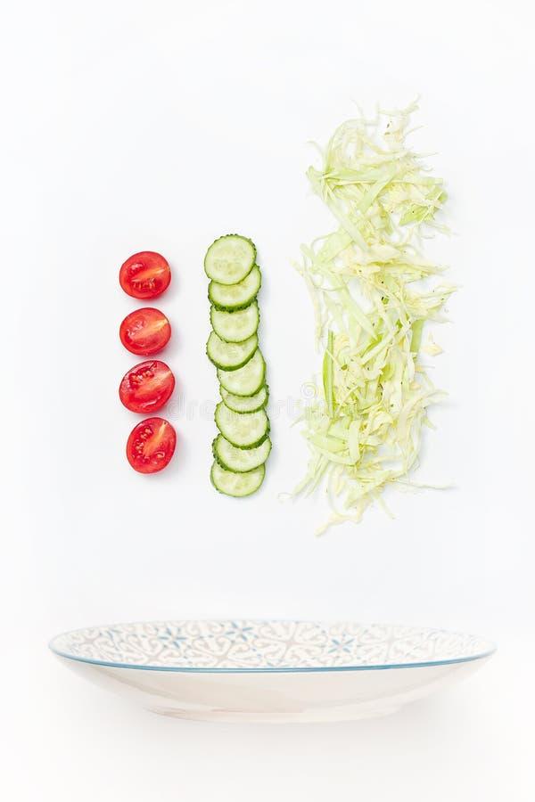 Salladbunken i flykten med grönsaker: tomat gurka, kål på vit bakgrund royaltyfri fotografi