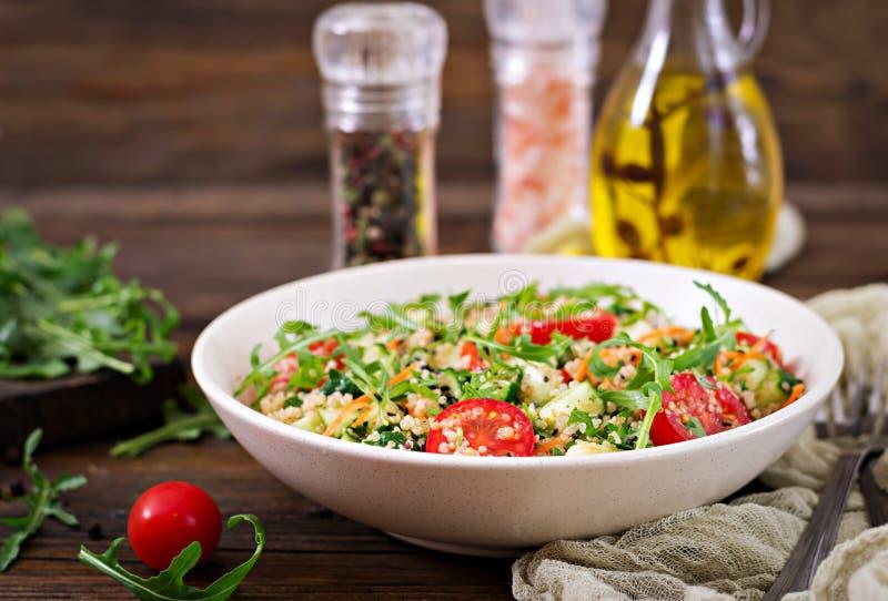 Sallader med quinoaen, arugula, rädisan, tomater och gurkan fotografering för bildbyråer
