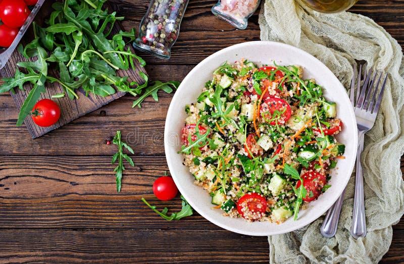 Sallader med quinoaen, arugula, rädisan, tomater och gurkan arkivbild