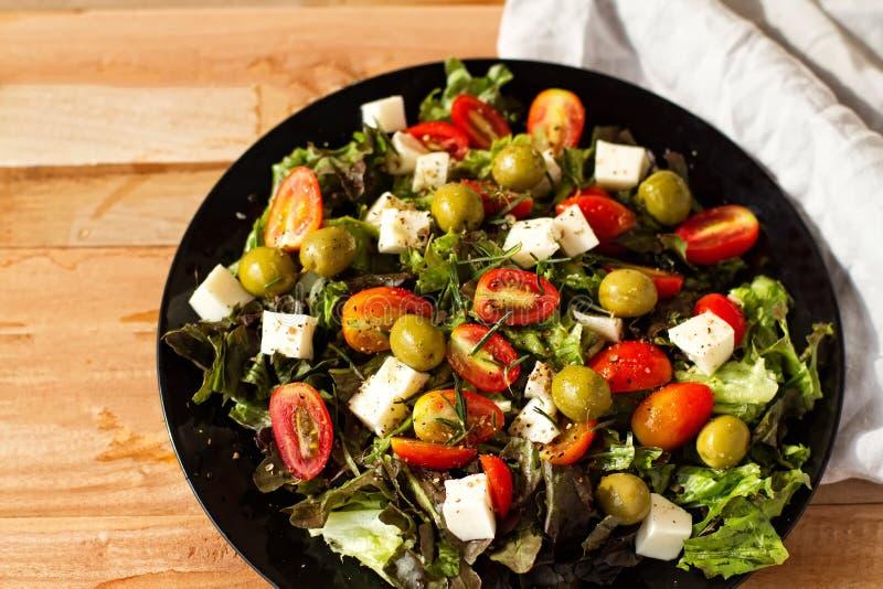 Salladgrek, ovoshny sallad, tomater, oliv, ost, sund mat, en banta med sallad, mycket aptitretande sallad på en trätabell fotografering för bildbyråer