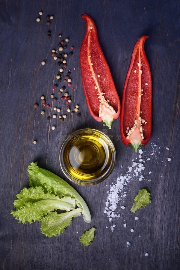 Salladingredienser: röd peppar, grönsallat, olivolja på lantlig träbakgrund Nya grönsaker, bästa sikt arkivfoton