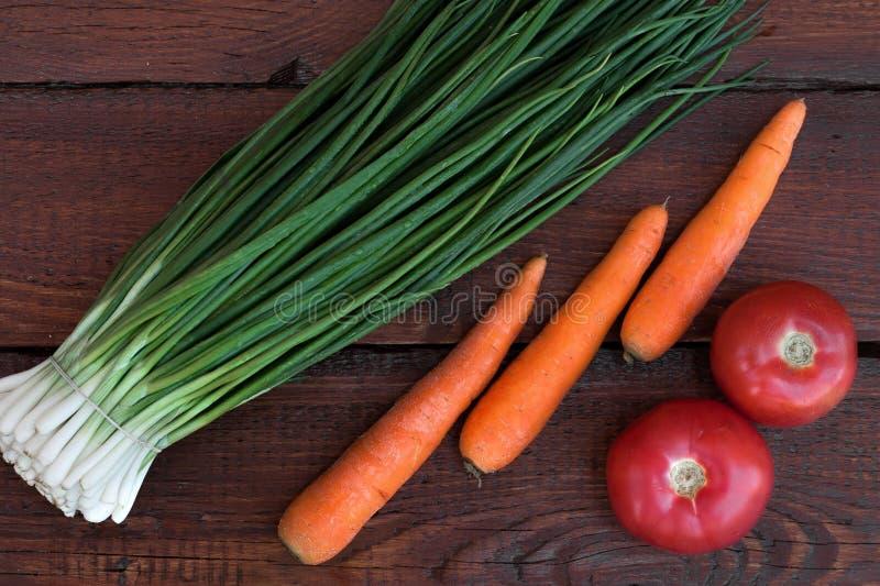 Salladslökar tvättade morötter, röda tomater arkivbild