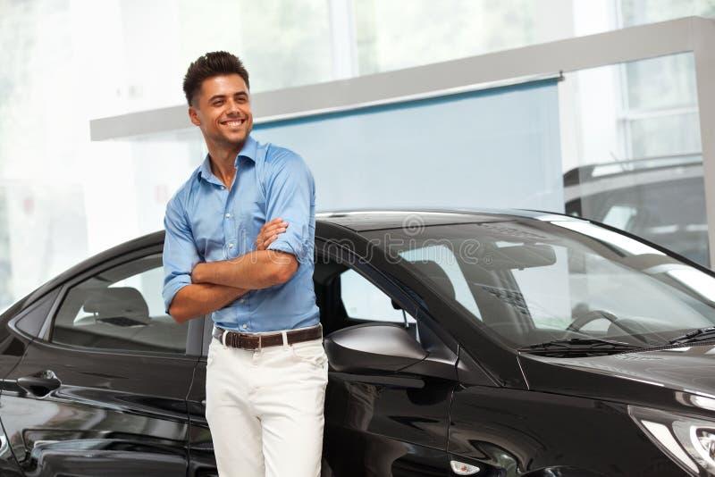 Salle d'exposition de voiture Homme heureux près de voiture de son rêve photo libre de droits