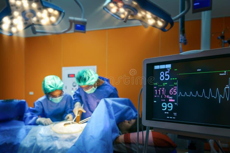 Salle d'opération avec le docteur et le moniteur d'impulsion photographie stock libre de droits
