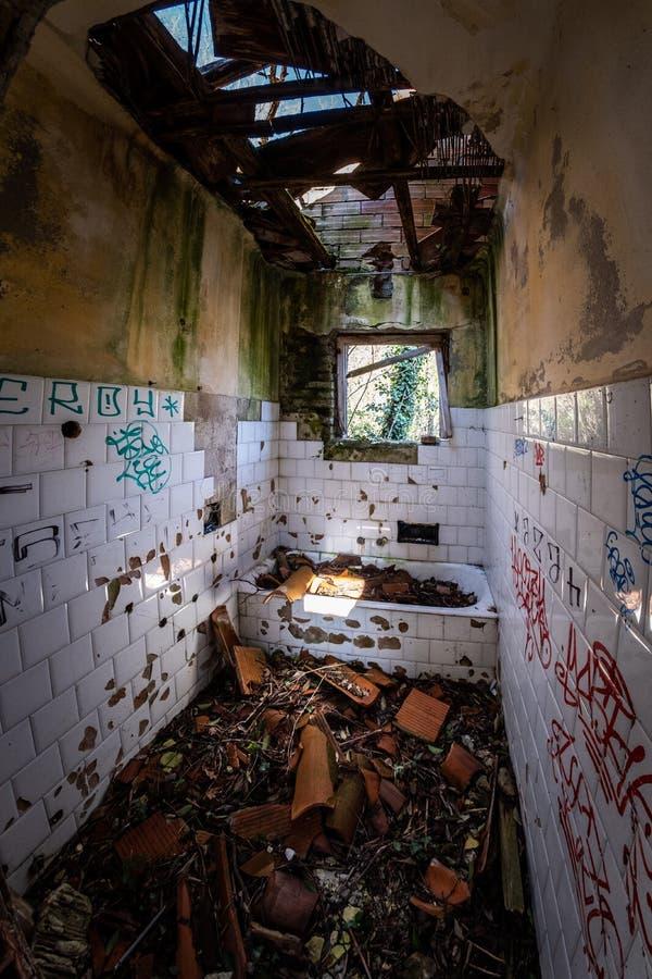 Salle de bains abandonnée par endroit perdu avec la baignoire complètement de tuiles, usines image libre de droits