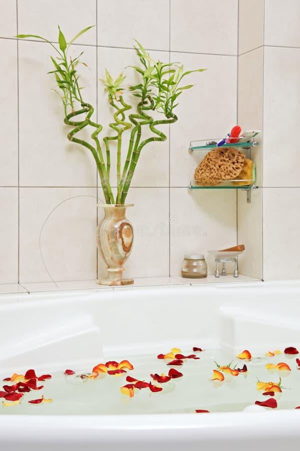 Salle de bains avec les pétales roses photographie stock