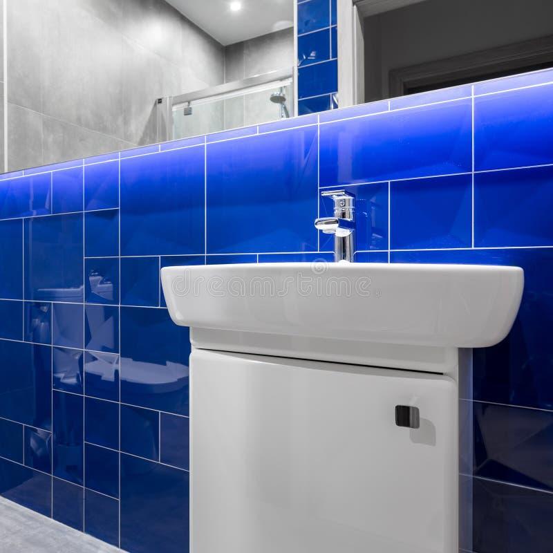 Salle de bains avec les tuiles brillantes bleues image stock