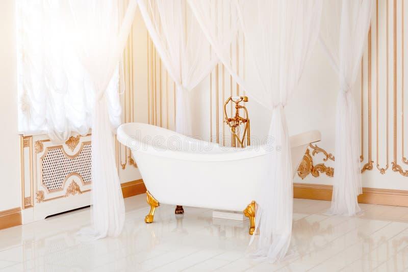 Salle de bains de luxe en couleurs les couleurs claires avec les détails et l'auvent d'or de meubles Intérieur classique élégant image stock