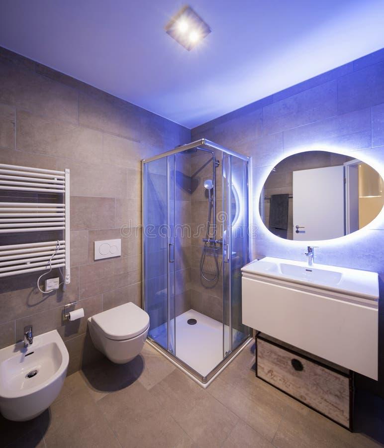 Salle de bains de marbre moderne avec le miroir rétro-éclairé image stock