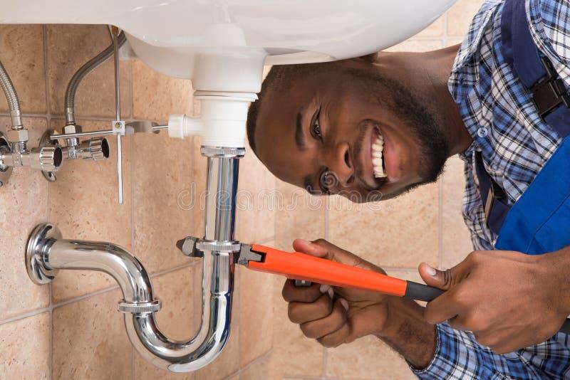 Salle de bains masculine heureuse de Repairing Sink In de plombier image stock
