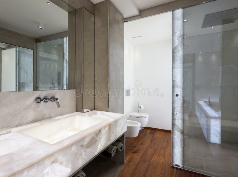 Salle de bains moderne avec du marbre et le parquet, personne images stock