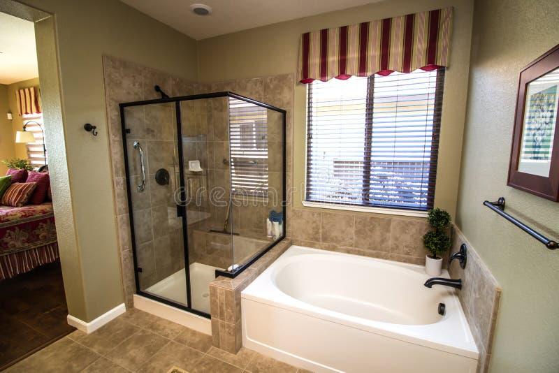Salle de bains moderne avec la douche et le baquet en verre photographie stock libre de droits
