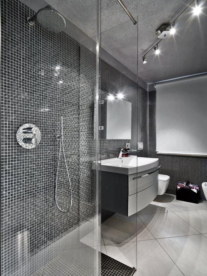 Salle de bains moderne avec le compartiment en verre de douche photographie stock