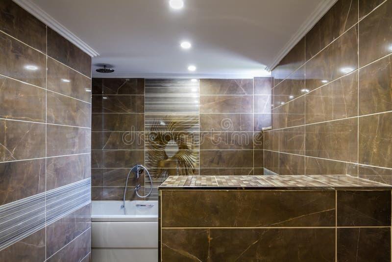 Salle de bains moderne décorée des murs de marbre, tube blanc de Bath photos libres de droits