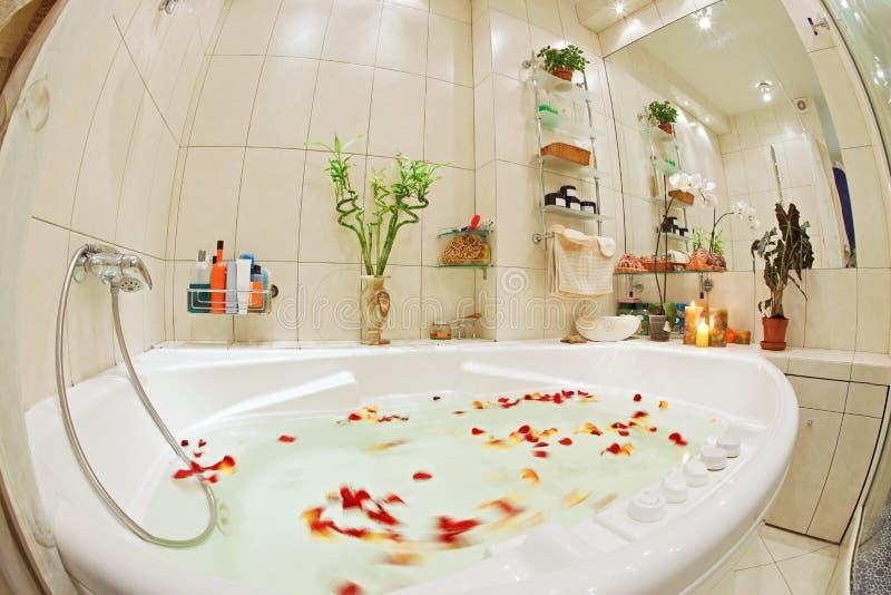 Salle de bains moderne dans des sons chauds avec le jacuzzi photographie stock