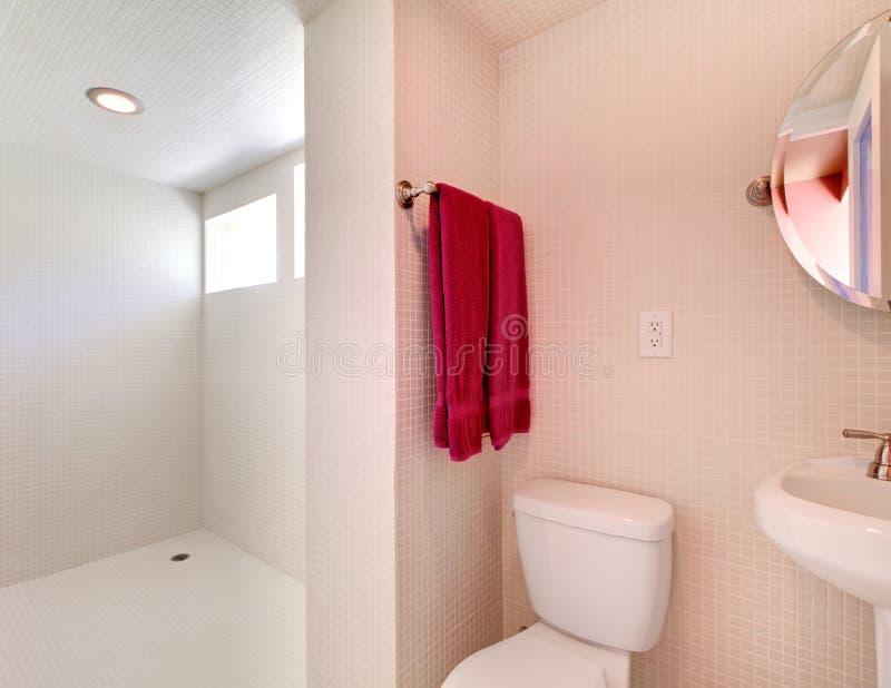 Salle de bains neuve blanche avec des tuiles tout autour. photo stock