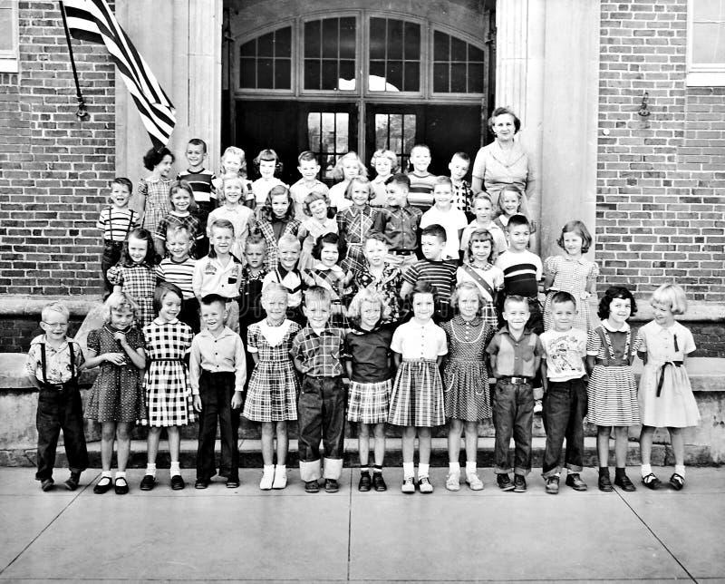 Salle de classe des enfants et d'un professeur devant le bâtiment photographie stock