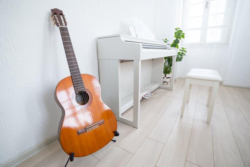 Salle de classe moderne de lumière du jour pour la musique de enseignement Guitare, pian blanc images stock