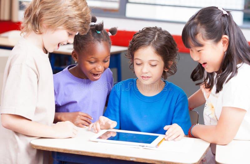Salle de classe multi-ethnique jouant avec le comprimé Concept heureux d'école images libres de droits