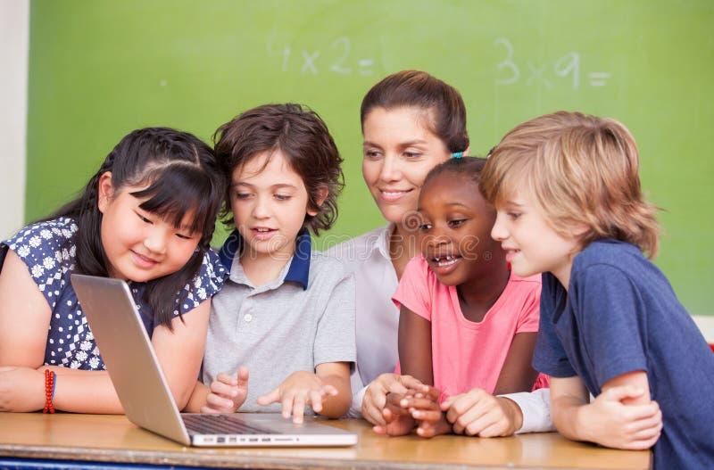 Salle de classe primaire interraciale apprenant à utiliser l'ordinateur portable avec le leur photographie stock libre de droits