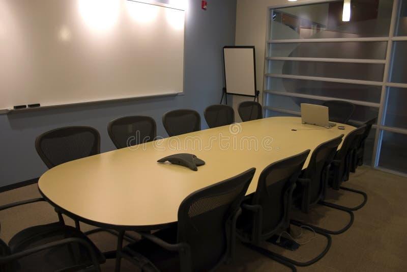 Salle de conférence avec un ordinateur portatif et un PDA sur la table photographie stock libre de droits